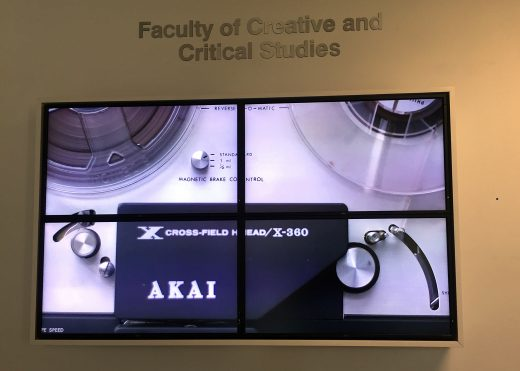 a video screen featuring a clip of a reel-to-reel machine turning