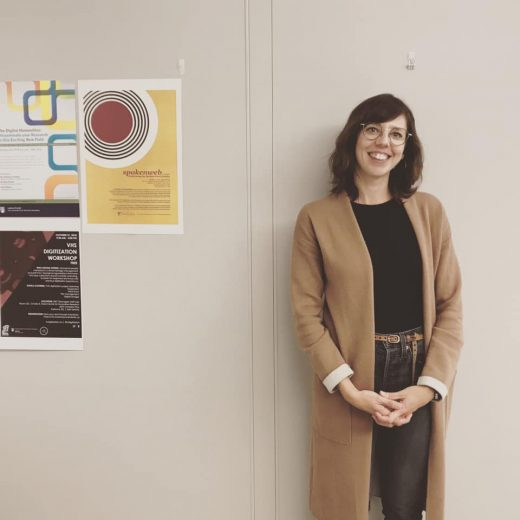 Carrie Karsgaard standing against a wall with posters