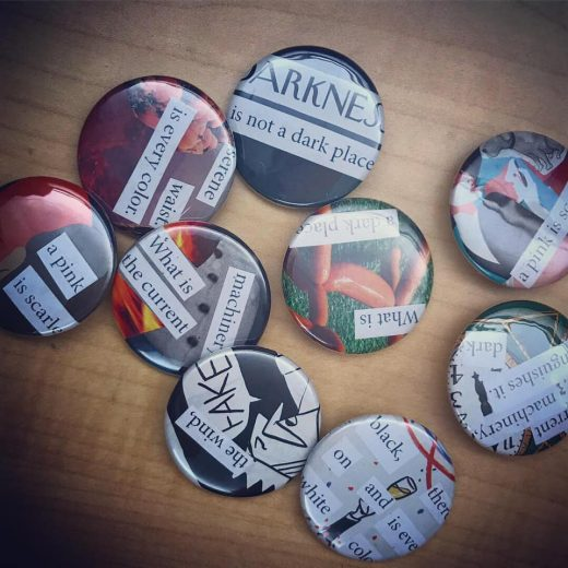 "A selection of the buttons made in the workshop. The buttons read ""Darkness is not a dark place"", ""serene waist is every colour,"" ""a pink is scarlet,"" ""what is a dark place,"" ""what is the current machinery,"" ""black on white and there is every colour,"" ""the wind, FAKE"" and finally ""the current machinery distinguishes it dark""."