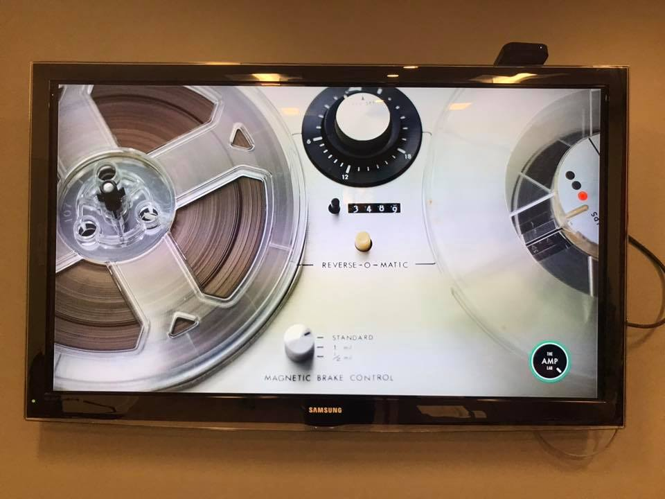 A screen shows a video clip of a reel-to-reel machine playing a tape
